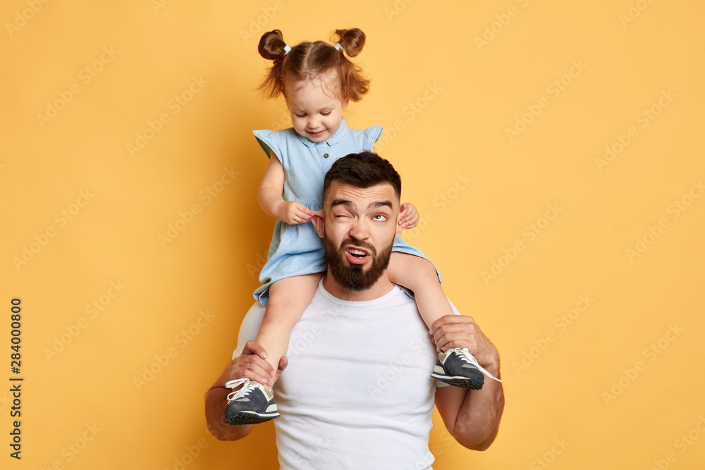 Fototapety, obrazy: daddy has been left one to sit with child and he cannot cope with it. kid got full control over situation.kid pulling her dad's ears
