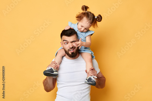 Obraz naughty behavior. parent cannot handle with kid with much energy. girl tiuching her dad's eyes while sittting on shoulders . close up photo. isolated yellow background. unacceptable kind of behaviour - fototapety do salonu