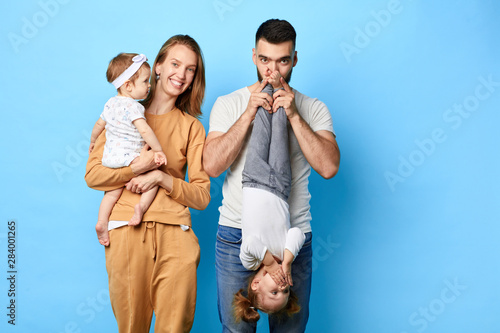 Obraz Loving husband and wife spending funny time with their kids. isolated blue background. studio shot.copy space - fototapety do salonu