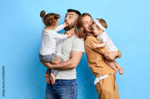 Obraz naughty children tormenting their parents, teasing dad and mommy. close up photo. crazy kids don't obey their parents. isolated blue background - fototapety do salonu