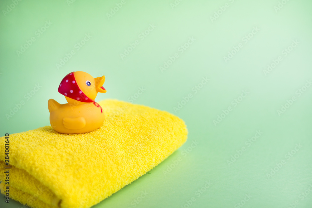 Fototapeta Yellow bath towel and rubber duck green background. Copy space.