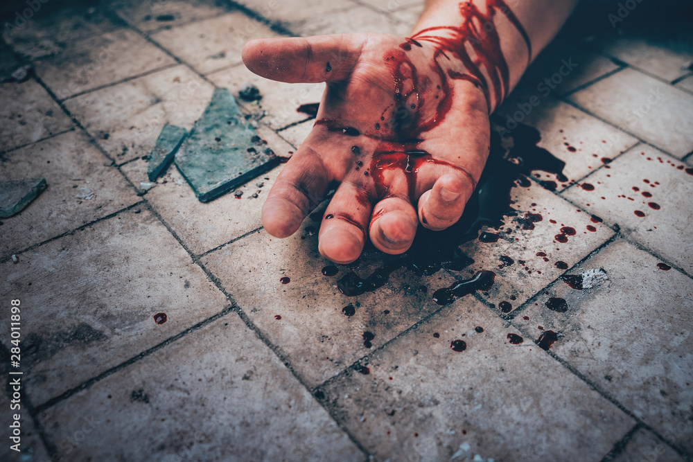 Fototapeta Crime scene with human hand in blood on floor of killed man by murder, dead body part close up.