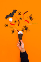 Halloween Holiday Background With Candy Corn And Decorations On An Orange Background. The Children's Hand Holds Ice Cream Cone With Halloween Decor.