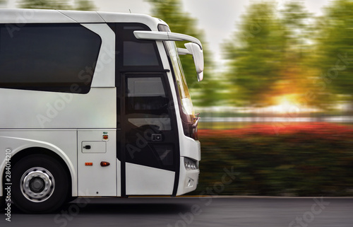 Fotografía Bus speeding by road in beautiful spring sunset at city