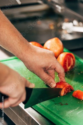 partial view of cook cutting tomatoes on chopping board in kitchen