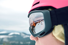 Close Up Portrait Of Snowboarder Woman At Ski Resort Wearing Helmet And Goggles With Reflection Of Mountains.