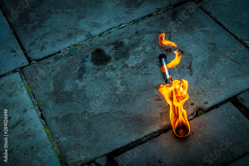 Canvas Print flaming torch lying on a stone floor prior to a juggling act in Bath, England