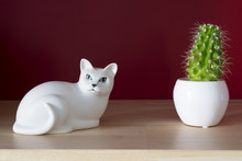 A White Ceramic Cat And Small Cactus On A Shelf With A Red Wall