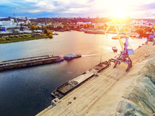 Aerial View Of Heavy Crane Loading Bulk Goods At Dnieper River Cargo Port Terminal In Kiev At Evening Sunset Time. Tugboat Pushes Barge With Sand After Loading. Industrial Inland Navigation