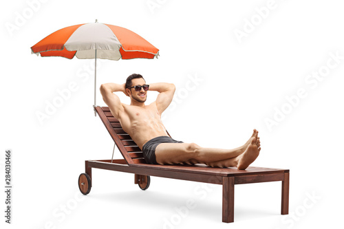 Young man lying on a sunbed under umbrella Fototapet