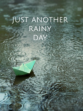 Just Another Rainy Day - Inspiration Quote On Abstract Rainy Background. Paper Boat In A Puddle. Bad Weather Backdrop. Paper Ship Floating In Water, Rainy Gloomy Weather. Shallow Depth, Soft Focus