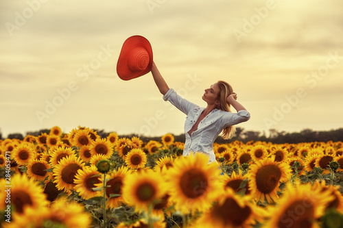 Tuinposter Zonnebloem A young woman in a wide-brimmed hat in a field with a flowering sunflower .