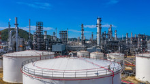 Oil​ Refinery​ And​ Petrochemical​ Plant Industrial Working With Fire And Blue Sky Background, Aerial View Oil And Gas Refinery At Day.