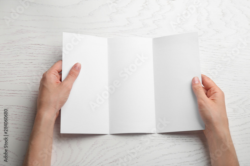 Spoed Foto op Canvas Londen Young woman holding blank brochure at white wooden table, top view. Mock up for design