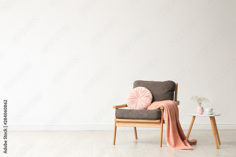 Fototapeta Stylish living room interior with comfortable armchair and wooden table near white wall. Space for text