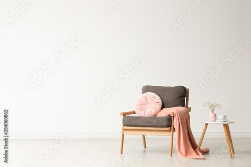 Valokuvatapetti Stylish living room interior with comfortable armchair and wooden table near white wall