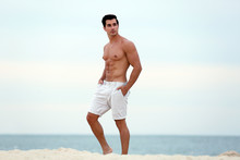Handsome Young Man Posing On Beach Near Sea