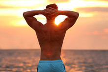 Handsome Young Man Posing On Beach Near Sea At Sunset