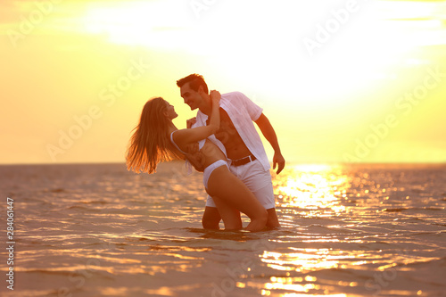 Poster Jaune de seuffre Happy young couple spending time together on sea beach at sunset