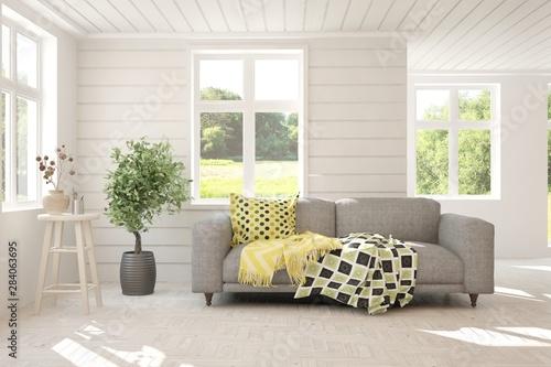 Fototapeta Stylish room in white color with sofa and summer landscape in window. Scandinavian interior design. 3D illustration obraz na płótnie