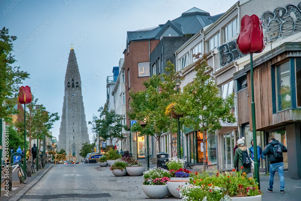Fototapeta REYKJAVIK, ICELAND - AUGUST 11, 2019: City street with Cathedral on the background. The city hosts most of the island population