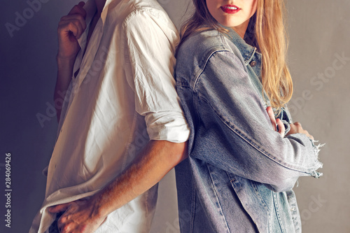 Fotografie, Obraz  Happy Young Couple Back To Back Each Other on a Grey Wall Background