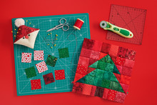 Christmas Tree Patchwork Block, Craft Mat, Bright Square Pieces Of Fabric, Pincushion Like Santa And Quilting Accessories On Red Background