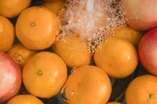 Hands Washing Fresh Orange And Apple.