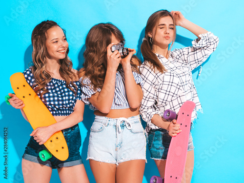 Fototapeta Three sexy beautiful stylish smiling girls with colorful penny skateboards.Women in summer hipster checkered shirt clothes posing near blue wall. Models taking pictures on retro camera obraz na płótnie