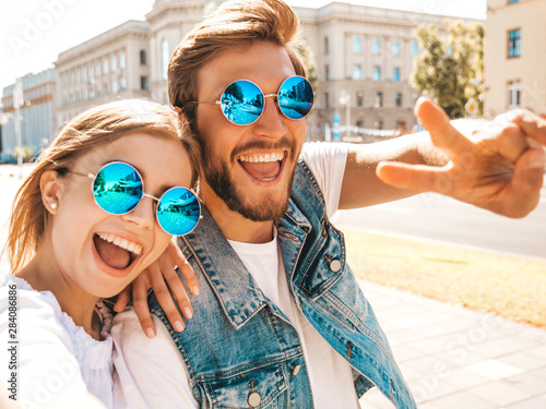 Fotografia  Smiling beautiful girl and her handsome boyfriend in casual summer clothes