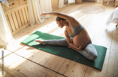 Photo Beautiful pregnant lady doing yoga exercise at home