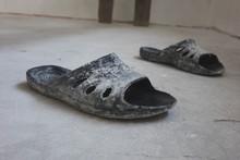 Black Rubber Flip-flops Standing On A Concrete Floor, The Concept Of Repair.