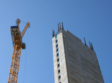 A Yellow Tower Crane Working On A Construction Site With A Tall Concrete Tower Against A Bright Blue Sky