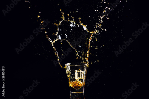 Bar Isolated shot of whiskey with splash on black background, brandy in a glass