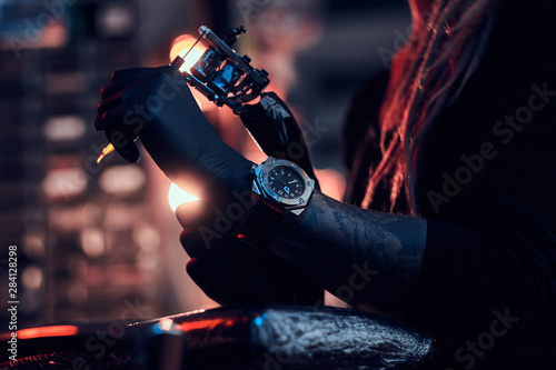 Canvas Print Hand in black glove of creative tattoo master with tattoo machine in it