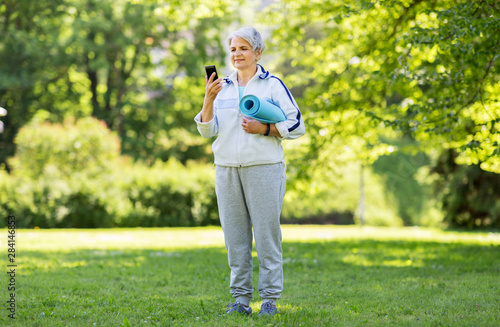 Stickers pour porte Pain fitness, sport and healthy lifestyle concept - happy smiling senior woman with exercise mat and smartphone at park