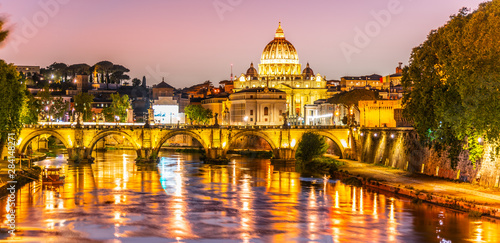 Wall Murals Light pink St Peters Basilica in Vatican and Ponte Sant'Angelo Bridge over Tiber River at dusk. Romantic evening cityscape of Rome, Italy