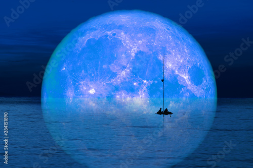 Photo reflection full harvest moon on sky and silhouette men on fishing boat on night
