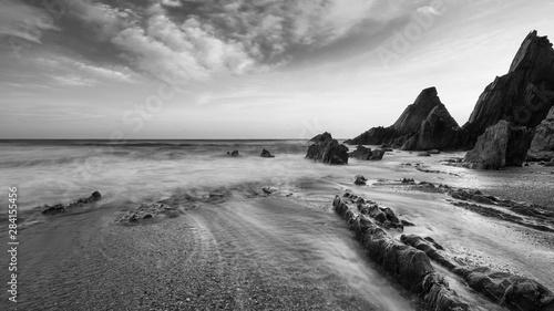 Foto auf Leinwand Rosa dunkel Stunning black and white sunset landscape image of Westcombe Beach in Devon England
