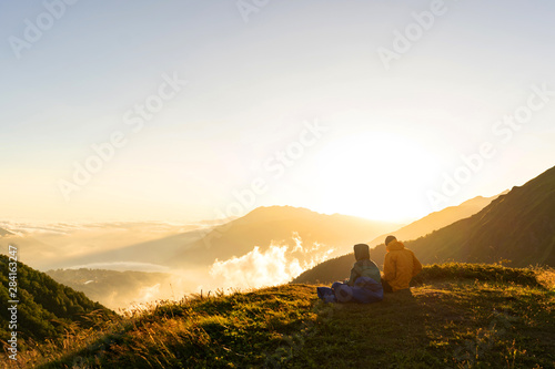 Photo  Loving couple in warm jackets sit on the top of the mountain Bzerpinsk cornice and enjoy the view of the clouds and the hacky sun