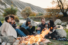 Smiling Charismatic Friends Different Races At Camping, Sitting Beside A Bonfire And Drinking Some Hot Drinks From Metallic Cups And Spending A Amazing Time Together.