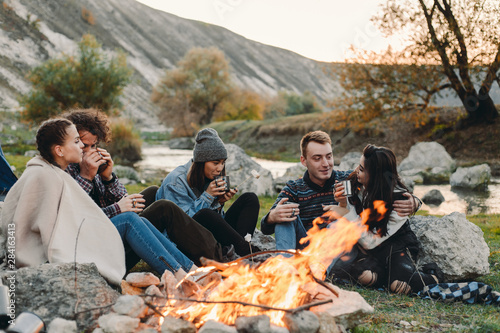 Smiling charismatic friends different races at camping, sitting beside a bonfire and drinking some hot drinks from metallic cups and spending a amazing time together Fototapete