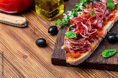 Photo  Delicious bread toast with natural tomato, extra virgin olive oil, Iberian ham, black olives and basil leaves