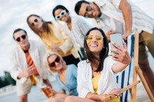 Selective Focus Of Attractive Young Woman Taking Selfie With Multicultural Friends Having Fun On Beach
