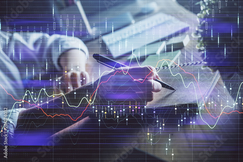 Financial forex charts displayed on woman's hand taking notes background. Concept of research. Double exposure