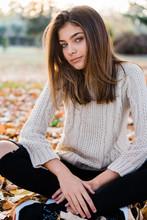 Teenage Girl Sitting In Autumn Park