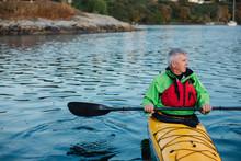 Active Mature Man Kayaking On The Ocean.