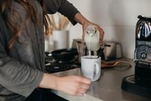 Woman Pouring Creamer Into Cof...