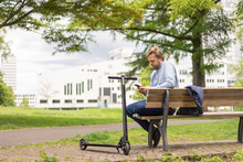 Businessman With E-Scooter Sitting On Bench In City Park Using Smartphone, Essen, Germany