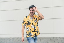 Young Man Wearing Flat Hat And Aloha Shirt, Laughing In Front Of Wall